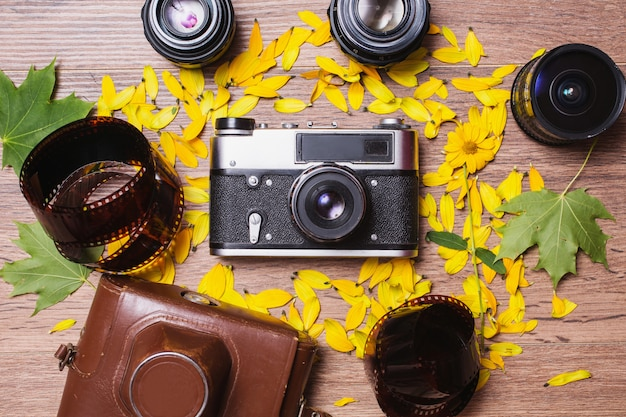 Atributos profissionais para fotografar. lentes e câmera vintage e filme sobre fundo de madeira. tiro arranjo de flores e tecnologia retro. folhas verdes. capa para uma câmera antiga.