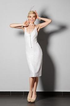 Atriz bonita no vestido retrô branco pérola dançando charleston