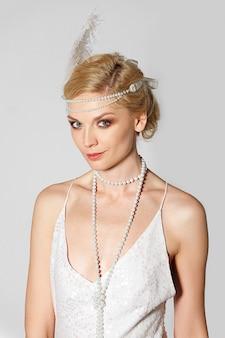 Atriz bonita no vestido retrô branco pérola e pluma no cabelo posando