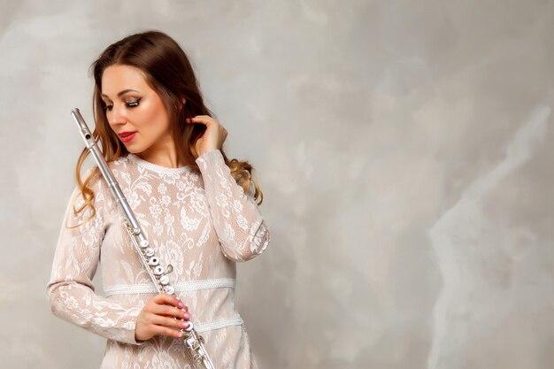 Atriz feminina de terno com flauta no fundo claro com a flauta na mão