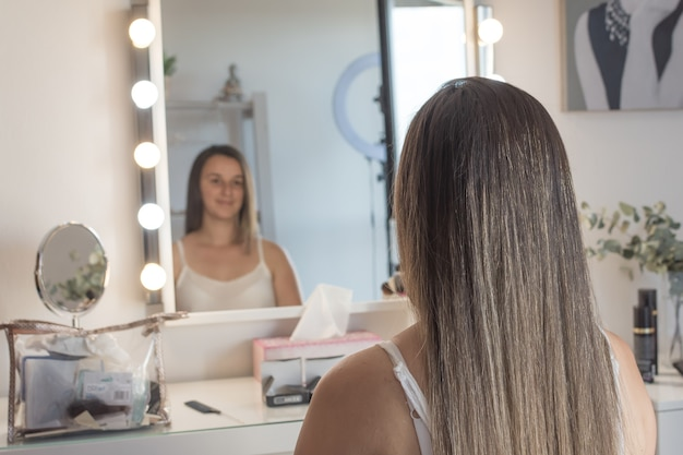 Atriz se olhando no espelho antes de atuar. sessão de cabelo e maquiagem.