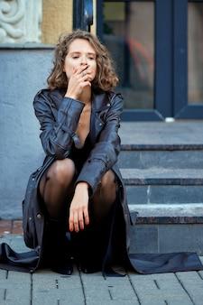 Atriz sentada na varanda com um pensamento de cigarro