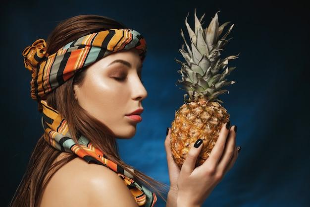 Attarctive mulher com bandana na testa, segurando o abacaxi nas mãos.