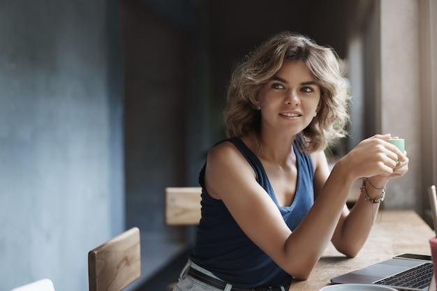 Attracitve moderno jovem loira encaracolado penteado virar intrigado sorrindo encantado segurar xícara bebida café trabalhando laptop, usar netbook estudando universidade tarefa, pesquisando freelance.