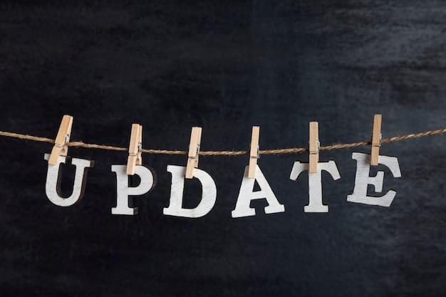 Atualização da palavra realizada no prendedor de roupa na corda contra a superfície preta.