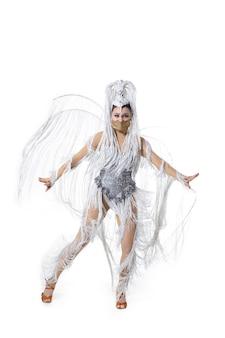Atuando. mulher jovem e bonita no traje do baile de carnaval com penas brancas, dançando sobre fundo branco. conceito de celebração de feriados, tempo festivo, dança, festa, felicidade. copyspace