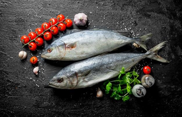 Atum de peixe cru com tomate cereja e dentes de alho na mesa rústica preta.