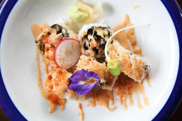 Atum de salmão e uramaki de abacate com molho picante em close up