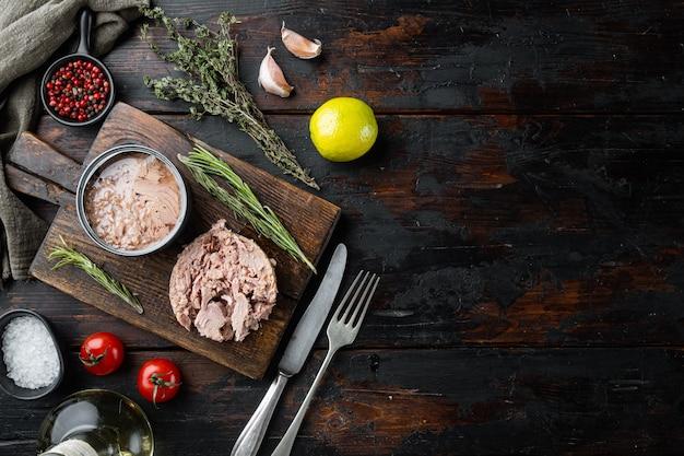 Atum enlatado, conservas de peixe, na tábua de madeira, na velha mesa de madeira escura com ervas e ingredientes, vista de cima plana lay