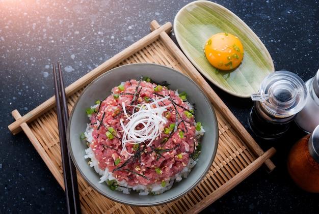 Atum fresco moído japonês com arroz na iluminação interna.