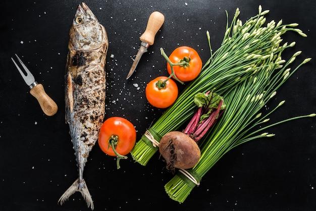 Atum grelhado com legumes em fundo escuro
