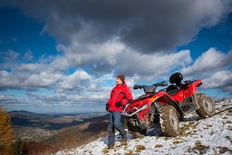 ATV quad moto perto de cara na encosta da montanha de neve