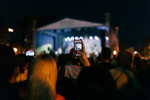 Audiência de gravação de vídeo e tirar fotos da banda no celular em concerto