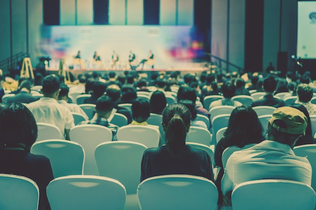 Audiência ouvindo oradores no palco da sala de conferências ou reunião do seminário