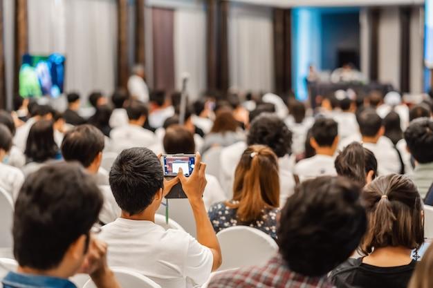 Audiência ouvindo os palestrantes e usando o celular tirando uma foto na sala de conferências