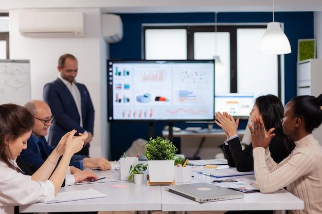 Audiência sorridente aplaudindo em um seminário de negócios após uma apresentação no sofá