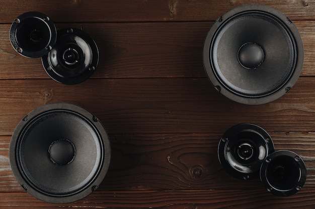 Áudio automotivo, alto-falantes pretos sobre uma superfície de madeira marrom.