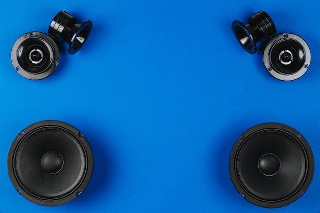 Áudio do carro, alto-falantes do carro, subwoofer preto sobre um fundo azul. copie o espaço
