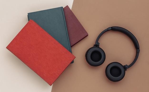 Áudio-livro. fones de ouvido e livros sobre fundo bege marrom. vista do topo.