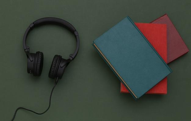 Áudio-livro. fones de ouvido e livros sobre fundo verde. vista do topo.