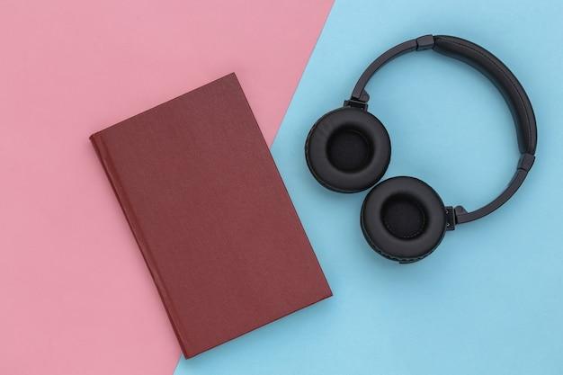 Áudio-livro. fones de ouvido e um livro sobre fundo azul-rosa pastel. vista do topo.