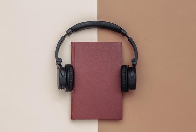 Áudio-livro. fones de ouvido e um livro sobre fundo bege marrom. vista do topo.