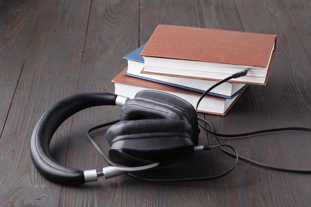 Audiobook conceito com fone de ouvido e livro de papel na mesa