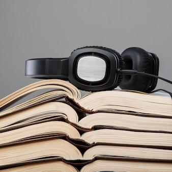 Audiobooks, fones de ouvido na pilha de livros