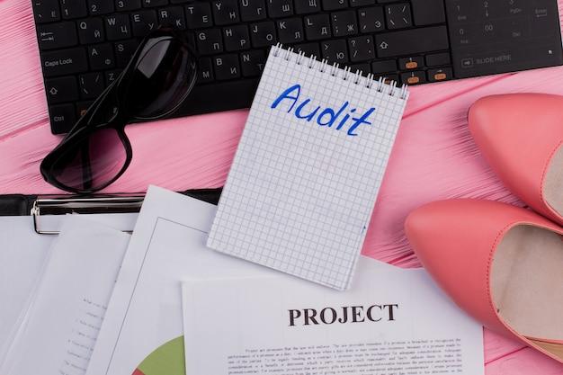 Audite o texto no bloco de notas com acessórios femininos na mesa rosa do escritório