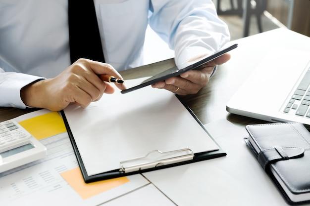 Auditor executivo de negócios usando o tablet para investimento de relatório de dados