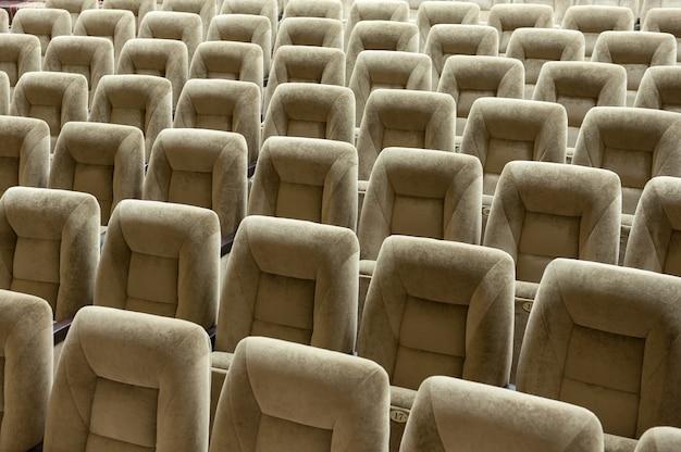 Auditório vazio com cadeiras bege, sala de teatro