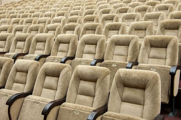 Auditório vazio com cadeiras bege, teatro ou sala de conferências