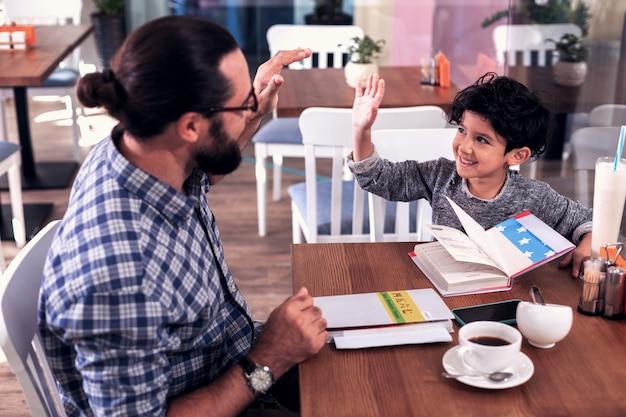 Aula com tutor. menino sorridente de cabelos escuros interessado em aproveitar a aula com o professor particular sentado no refeitório