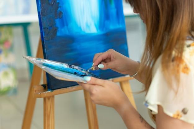 Aula de arte, desenho e conceito de criatividade aluna sentada em frente ao cavalete com paleta e