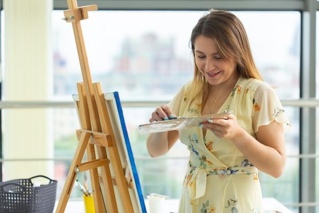 Aula de arte e conceito de desenho - artista mulher trabalhando na pintura em estúdio.
