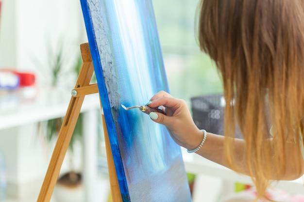 Aula de arte e desenho conceito mulher artista trabalhando em pintura em estúdio closeup