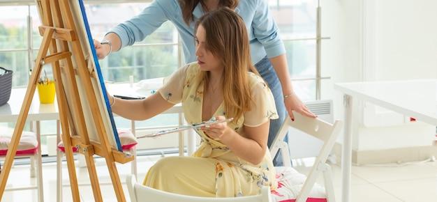 Aula de arte e o conceito de desenho - artista mulher trabalhando na pintura em estúdio.