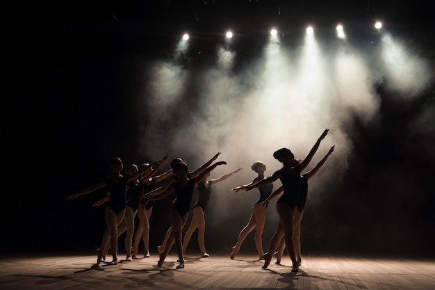 Aula de balé no palco do teatro com luz e fumaça.