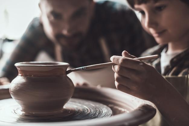 Aula de cerâmica. garotinho desenhando em um pote de cerâmica na aula de cerâmica, enquanto um homem de avental está perto dele