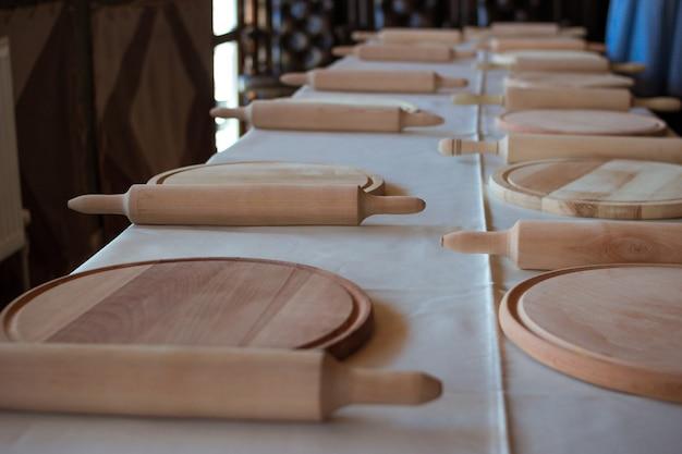 Aula de culinária de pizza, culinária. muitas tábuas de corte de madeira e pinos do rolo na mesa comprida com toalha de mesa branca. detalhes para preparar comida, refeição na cozinha