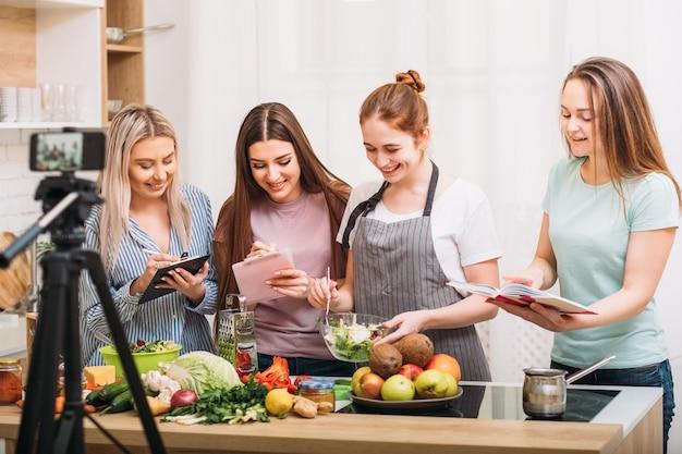 Aula de culinária. nutrição saudável. grupo de jovens fêmeas escrevendo a receita. gravação de vídeo em smartphone.