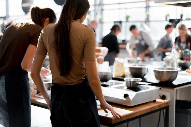 Aula de culinária. vista traseira do processo de cozimento. diferentes pessoas irreconhecíveis na cozinha. oficina de culinária.