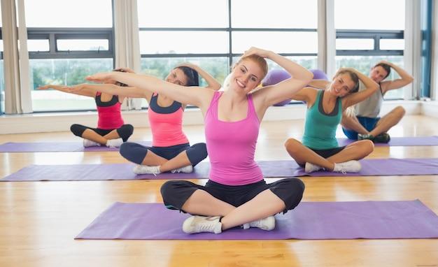 Aula de fitness e instrutor esticando as mãos em tapetes de ioga