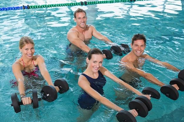 Aula de fitness feliz fazendo hidroginástica com halteres de espuma