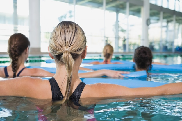 Aula de fitness feminino fazendo hidroginástica com rolos de espuma