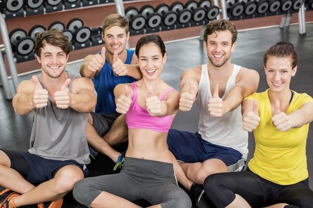 Aula de fitness, mostrando os polegares para cima no ginásio