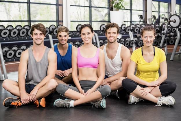 Aula de fitness sentado no chão no ginásio