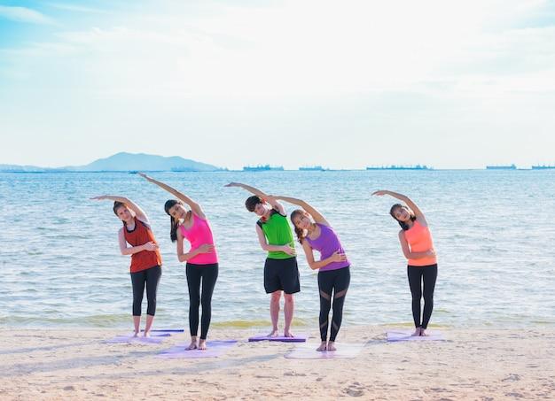 Aula de ioga na praia do mar à noite, grupo de pessoas que faz as curvaturas paradas positivas