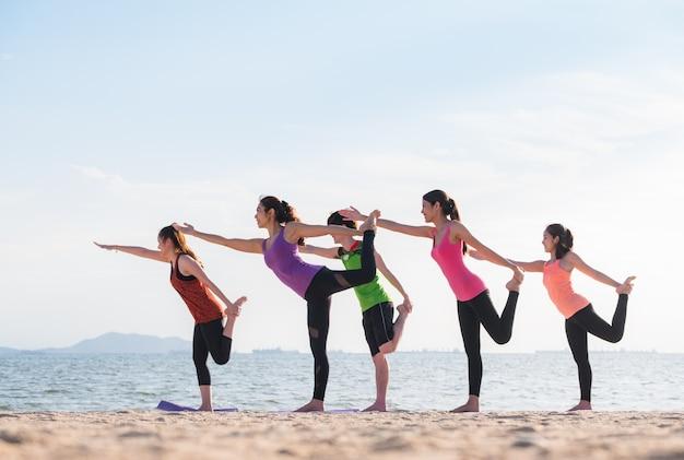 Aula de ioga na praia do mar à noite, grupo de pessoas que faz o senhor das poses de dança