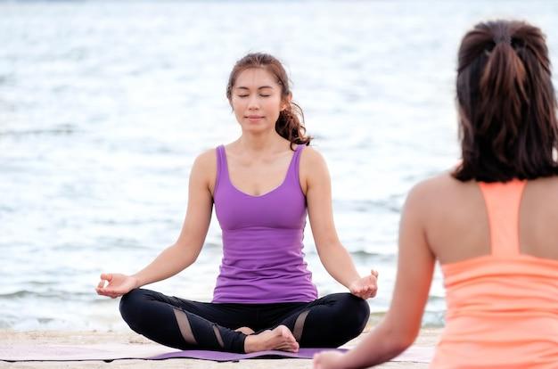 Aula de ioga na praia do mar, mestre guru fazendo pose de lótus com molusco